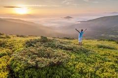 站立在一座山顶部的远足者用被举的手和enjoyi 库存照片