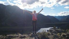 站立在一座山顶部的远足者年轻愉快的妇女用手rised  库存图片