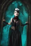 站立在一座老城堡的门道入口的可怕女孩 免版税图库摄影