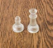 站立在一张木桌上的两个玻璃棋子 库存照片