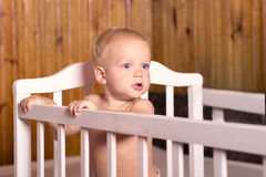 站立在一张白色床上的逗人喜爱的婴孩 幼儿的托儿所在乡间别墅里 学会的小男孩站立在他的小儿床 免版税库存照片