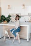 站立在一张高脚椅子的厨房用桌附近的女孩 明亮,白色厨房 愉快的微笑的女孩在厨房里 女孩 库存图片
