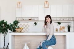 站立在一张高脚椅子的厨房用桌附近的女孩 明亮,白色厨房 愉快的微笑的女孩在厨房里 女孩 库存照片