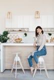 站立在一张高脚椅子的厨房用桌附近的女孩 明亮,白色厨房 愉快的微笑的女孩在厨房里 女孩 免版税库存图片