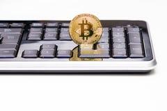 站立在一张黑键盘和白色书桌的金黄Bitcoin硬币 关键结尾轰鸣声Bitcoin 说明社论 免版税库存图片