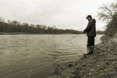 站立在一快速流动的ri的银行的早期的春天渔夫 免版税图库摄影