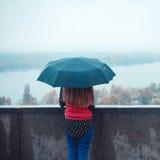 站立在一把伞下的浪漫妇女在雨天 免版税库存图片