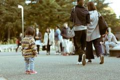 站立在一条拥挤步行街道上的小孩在代代木公园 免版税库存图片