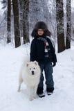 站立在一条白色狗旁边的帽子的男孩 免版税库存图片