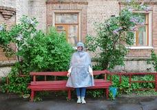 站立在一条红色长凳附近的雨衣的女孩 免版税库存照片