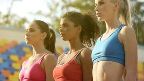 站立在一条线的三个年轻女运动员,殷勤地听教练 免版税库存照片