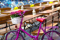 站立在一条老街道上的桃红色自行车 免版税库存照片