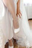 站立在一条腿和第二条腿的新娘拉扯了白色 免版税库存照片
