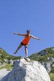 站立在一条腿的俏丽的妇女远足者用被举的手 免版税图库摄影
