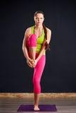 站立在一条腿的紫罗兰色瑜伽席子的sportwear的年轻美丽的妇女反对黑暗的背景 库存照片