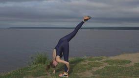 站立在一条腿,平衡训练,瑜伽的妇女 免版税库存图片