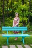 站立在一条长凳附近的一件明亮的蓝色礼服的美丽的年轻红发妇女在庭院里 免版税库存图片