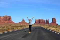 站立在一条高速公路的妇女在沙漠 免版税库存图片