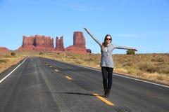 站立在一条高速公路的妇女在沙漠 图库摄影