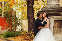 站立在一根老灰色柱子后的新婚佳偶微笑 免版税库存图片