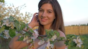 站立在一棵开花的苹果树的一名年轻白种人妇女的画象 影视素材