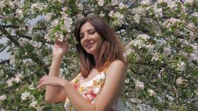 站立在一棵开花的苹果树的一名年轻白种人妇女的画象 股票录像