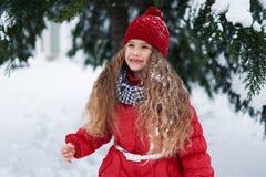 站立在一棵树下的女孩在冬天 库存照片