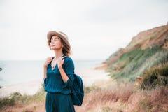 站立在一棵草的年轻行家妇女夏天画象在晴天 免版税库存照片