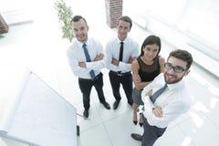 站立在一空白的flipchart旁边的企业队 免版税库存图片