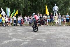 站立在一辆摩托车的前轮在托马斯加里宁Verhovazhe沃洛格达州地区表现的,俄罗斯 库存照片