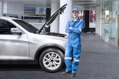 站立在一辆残破的汽车附近的欧洲技工 库存图片