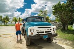 站立在一辆老卡车旁边的少年 库存照片