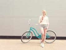 站立在一辆绿色葡萄酒自行车附近和拿着一个杯子coffeehave乐趣和好心情的年轻性感的白肤金发的妇女看在照相机a 免版税库存照片
