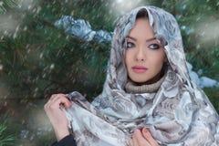 站立在一件围巾和温暖的毛线衣的雪下的美丽的可爱的女孩在冬天森林里在树附近 免版税库存图片