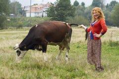 站立在一头母牛附近的村庄妇女在草甸 库存图片