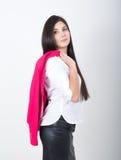 站立在一件皮革裙子和白色女衬衫的年轻人相当亭亭玉立的亚裔妇女 拿着在shoulderl的一件红色夹克 免版税库存图片