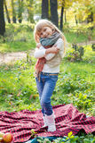 站立在一绿色公园和微笑的美丽的矮小的长发白肤金发的女孩 免版税库存图片