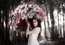 站立在丁香伞下的青少年的女孩在庭院里 免版税库存图片