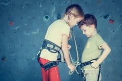 站立在上升的岩石墙壁附近的兄弟和姐妹 免版税库存照片