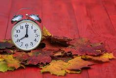 站立在下落的澳大利亚中的一张红色木桌上的老金属时钟 图库摄影