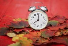 站立在下落的秋天中的一张木桌上的老金属时钟 免版税图库摄影