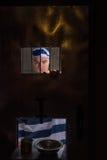 站立在与一个孔的铁门后的囚犯supplyin的 库存照片