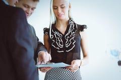 站立在与一个文件夹的前景的女商人在她的手上 库存照片