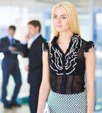 站立在与一个文件夹的前景的女商人在她的手上 图库摄影
