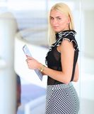 站立在与一个文件夹的前景的女商人在她的手上 库存图片