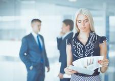 站立在与一个文件夹的前景的女商人在她的手上 免版税库存照片