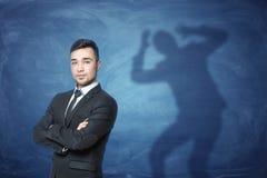 站立在与一个阴影的蓝色背景的商人用在头的手在他后 免版税库存图片