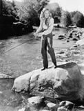站立在与一根钓鱼竿的一个岩石的妇女(所有人被描述不更长生存,并且庄园不存在 供应商保单 库存照片