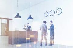 站立在与三个时钟的一个办公室柜台附近的人们,被定调子 免版税库存图片