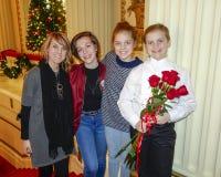 站立在与中年母亲和姐妹的一层红色楼梯的微笑的十岁的女孩 图库摄影